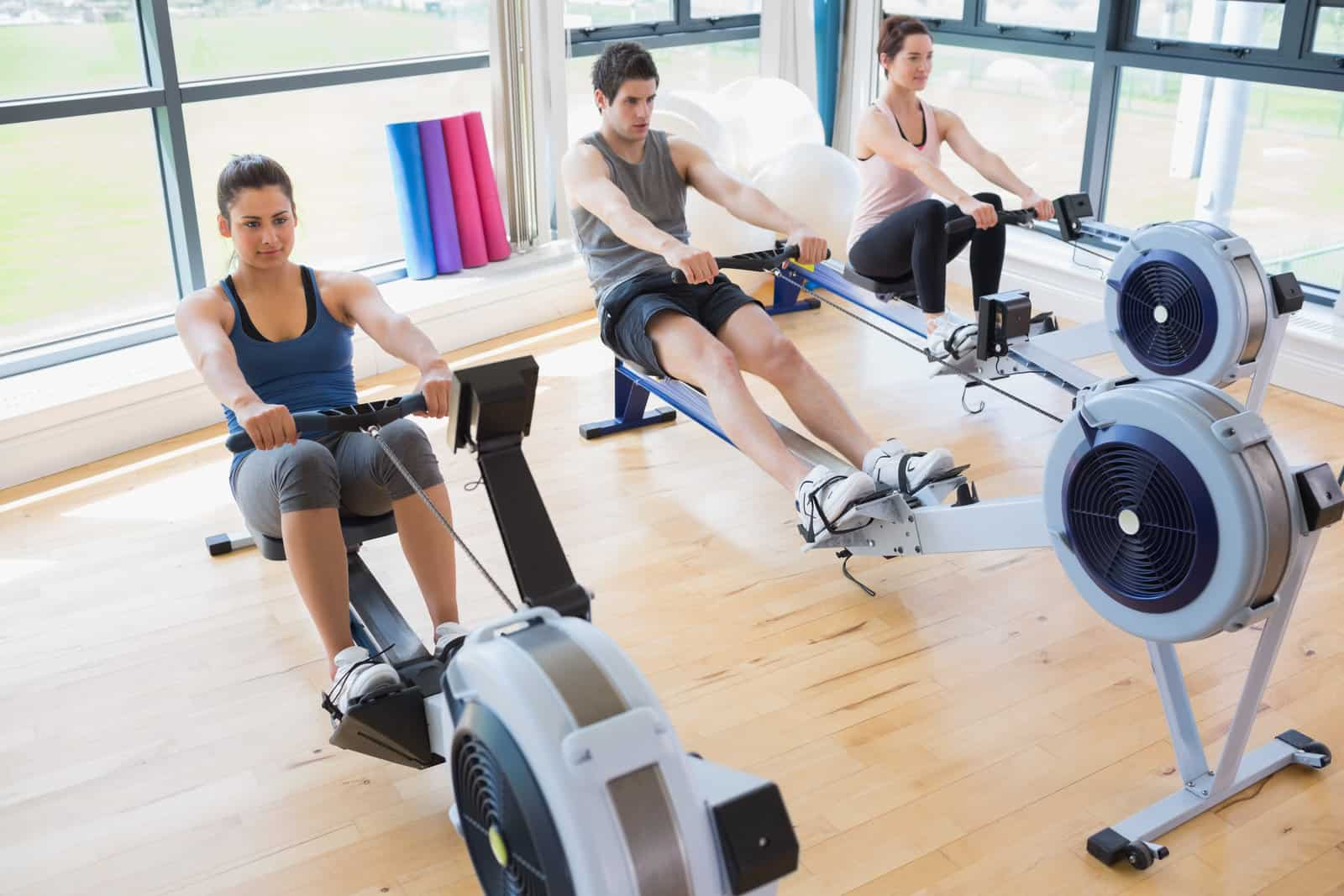 people at the gym working out discovering the benefits of using a rowing machine