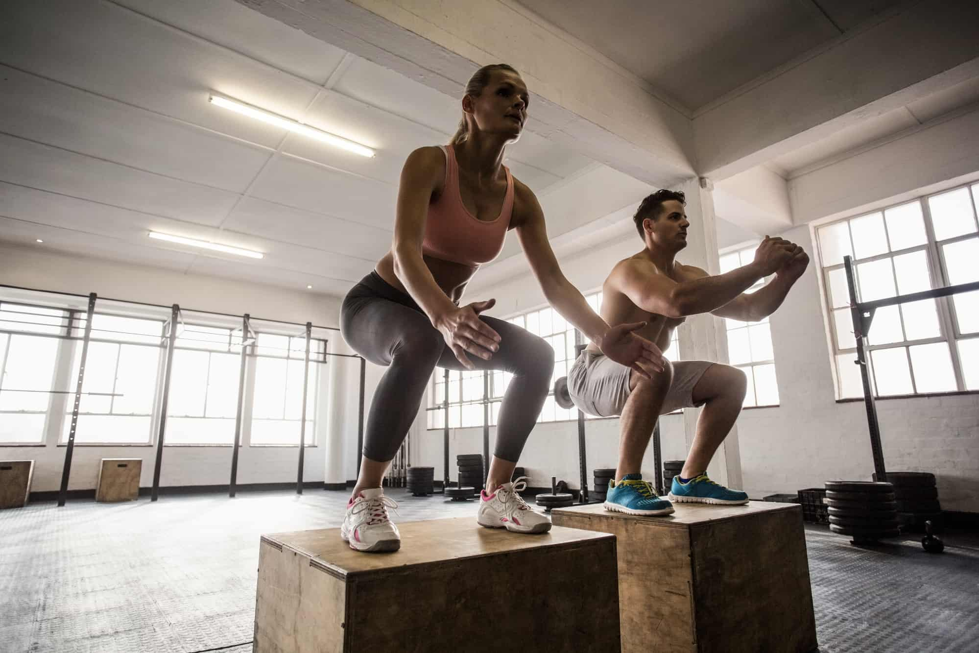 man and lady exercising at crossfit class