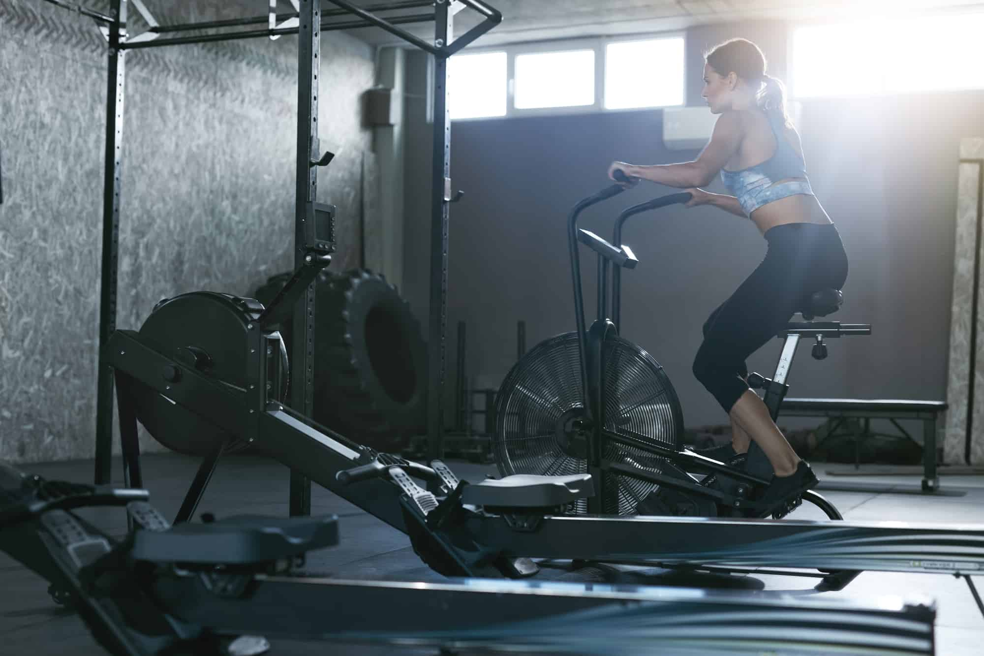 lady at gym working out on an assault bike crossfit