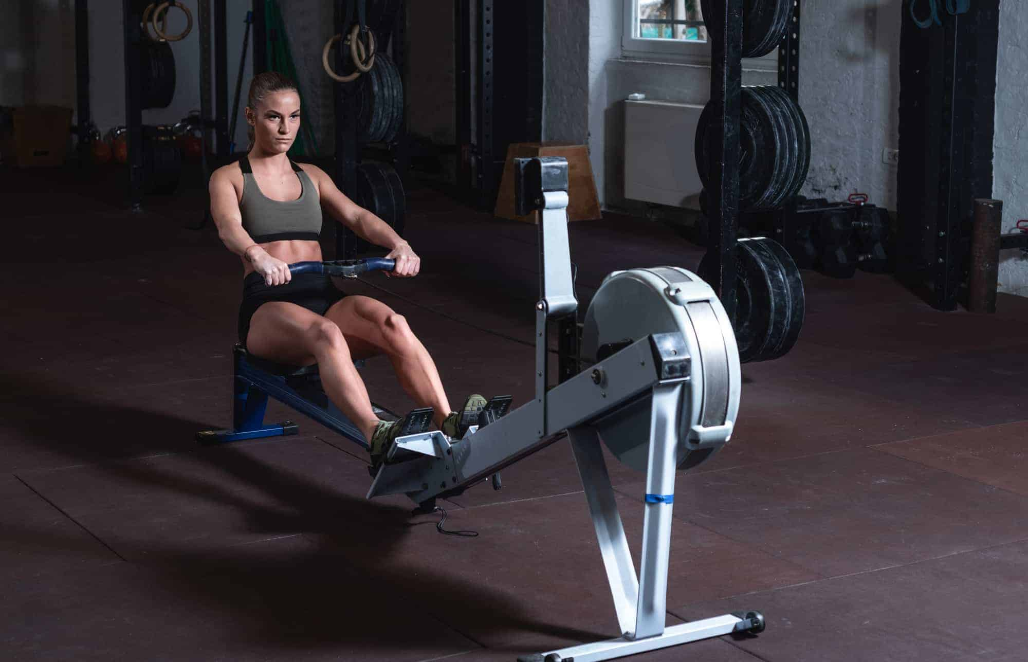 lady reading monitor on machine to see how many calories burned rowing