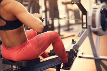 Lady working out on rowing machine in orange exercise leggings