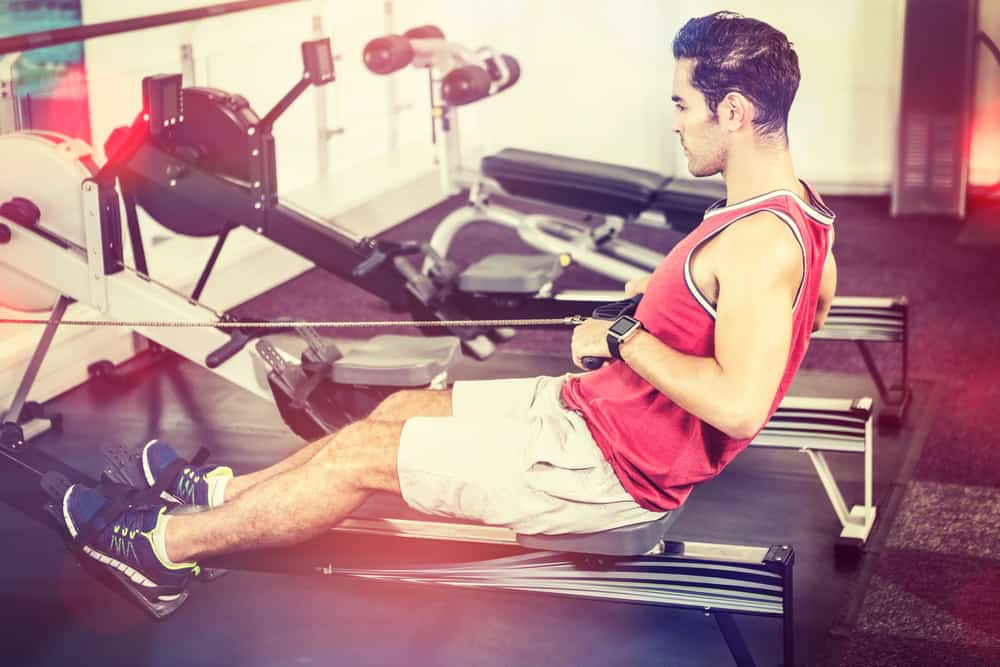 man at gym safely rowing after a hip replacement