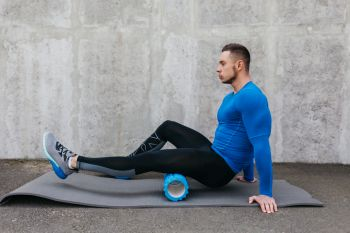 man on a foam roller to prevent hip pain after rowing machine
