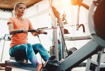 lady working out at gym to see are rowers good exercise