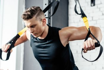 man working out doing rowing exercise with bands
