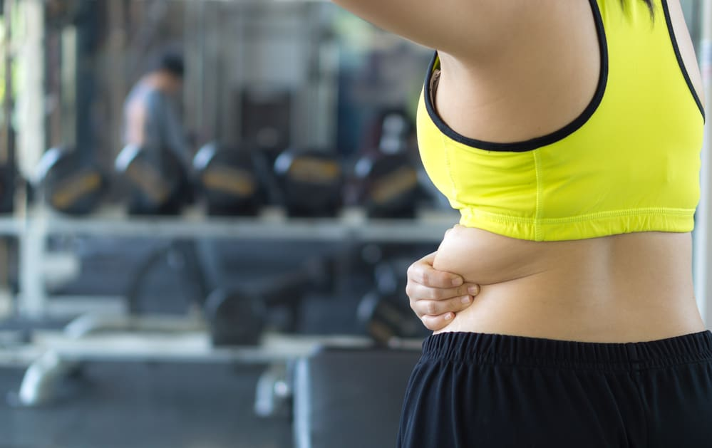 lady doing gym exercises for back fat