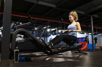 lady training at gym do a rowing machine fat loss program