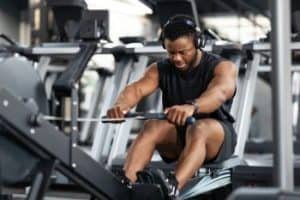 man exercising at gym to lose weight rowing